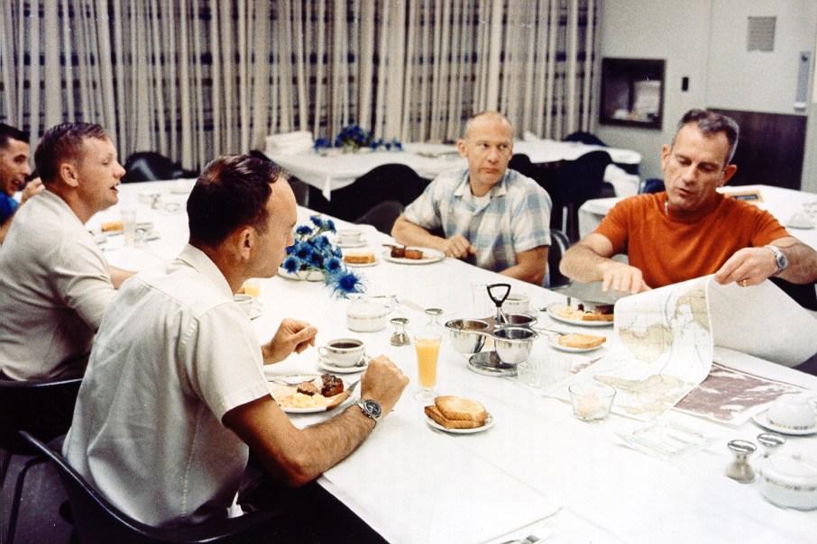 Deke Slayton (de naranja), desayunando con la tripulación del Apolo 11